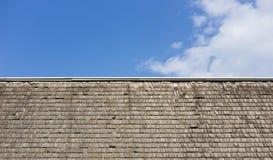Tetto di legno avariato dell'assicella contro un cielo blu con le nuvole fotografia stock libera da diritti