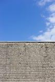 Tetto di legno avariato dell'assicella contro un cielo blu con le nuvole immagine stock