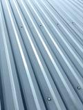 Tetto grigio ondulato del metallo con i ribattini come fondo Fotografie Stock Libere da Diritti
