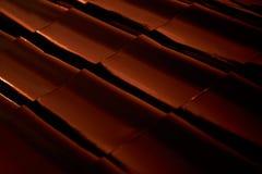Tetto-mattonelle astratte di profilo del metallo del primo piano al tramonto Immagini Stock
