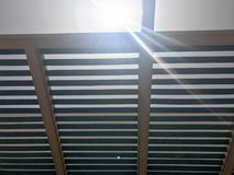 Tetto moderno del progettista all'aperto con i fori dei fasci con i bordi contro il sole fotografia stock