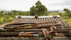Tetto ondulato Grungy d'annata con le valvole abbandonate del tubo flessibile dei tubi di acqua e Rusty Metal Junk di plastica -  fotografie stock libere da diritti