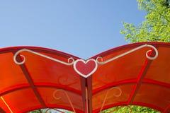Tetto rosso delle dépendance con una forma del cuore su un fondo di Immagini Stock Libere da Diritti