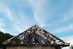 Tetto trascurato con una certa assicurazione su delle mattonelle di tetto ancora immagine stock