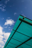 Tetto verde con costruzione sul fondo del cielo blu Fotografia Stock