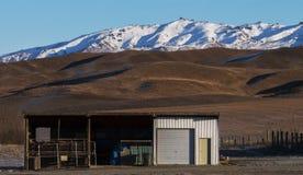 Tettoia dell'azienda agricola in Sun di mattina con il contesto della montagna Immagine Stock