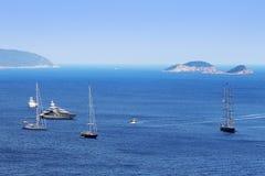 Teure Boote auf großem Meer mit Insel Stockfotografie