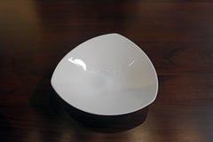 Teure dreieckige geformte Luxusporzellanplatte auf einer Einstellung des eichenen Tischs Stockfotos