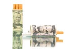 Teure Gewohnheit. Geld und Zigaretten auf weißem Hintergrund Stockfoto