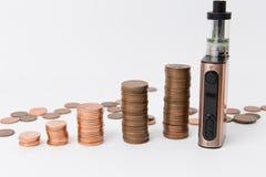 Teures elektrisches Zigarette ecigarette und Stapel Münzen, die auf der Seite am weißen Hintergrund stehen Stockfotografie
