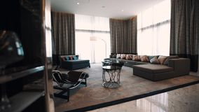 Teures Wohnzimmer Innen, langes Sofa großer Fernsehschirm, helle helle Fenster stock video footage