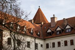 Teutonic castle and red brick tower in the park in the autumn season. A high tower with a sloping red brick roof on a hill. Royalty Free Stock Photo