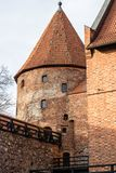Teutonic castle and red brick tower in the park in the autumn season. A high tower with a sloping red brick roof on a hill. Stock Photos