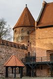 Teutonic castle and red brick tower in the park in the autumn season. A high tower with a sloping red brick roof on a hill. Royalty Free Stock Photography