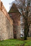 Teutonic castle and red brick tower in the park in the autumn season. A high tower with a sloping red brick roof on a hill. Stock Photo