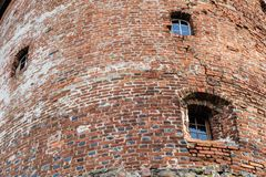 Teutonic castle and red brick tower in the park in the autumn season. A high tower with a sloping red brick roof on a hill. Royalty Free Stock Photos