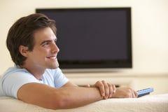 Tevê de observação do tela panorâmico do homem em casa Fotos de Stock Royalty Free