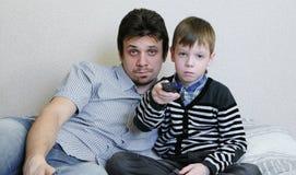Tevê de observação que encontra-se no sofá O menino furado e seu paizinho estão olhando a tevê e os interruptores os canais Fotos de Stock