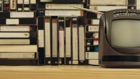 Tevê pequena velha contra o fundo dos video tapes Câmera que move-se horizontalmente video estoque