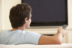 Tevê de observação do tela panorâmico do homem em casa Imagens de Stock