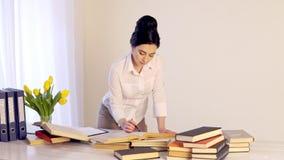 Teveel werk vermoeide slaperige jonge vrouwenzitting bij haar bureau met boeken stock videobeelden