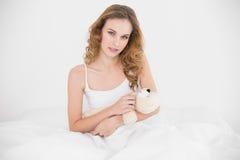 Tevreden aantrekkelijke donkerbruine knuffelende teddybeer Royalty-vrije Stock Foto