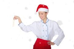 Tevreden Aziatische chef-kok in Kerstmisuitrusting met eetstokjes onder sneeuw stock foto's