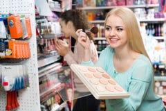Tevreden charmant vrouwelijk klant het kopen huidpoeder stock foto