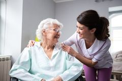 Tevreden en gelukkige hogere vrouwenpatiënt met verpleegster stock afbeeldingen