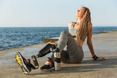 Tevreden gehandicapte atletenvrouw met prothetisch been stock foto