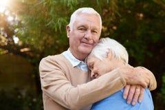 Tevreden hogere mens die affectionately zijn vrouw buiten koesteren stock fotografie