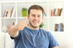 Tevreden huiseigenaar die u met omhoog duimen bekijken stock foto
