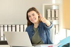 Tevreden intern met duimen omhoog op kantoor stock foto's