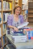 Tevreden kalme vrouwelijke bibliothecaris die boeken terugkeren royalty-vrije stock foto