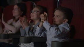 Tevreden kinderen die in bioskoop toejuichen Onweer van applaus in bioskoop stock footage