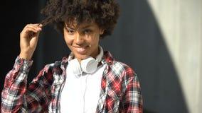 Tevreden krullende haired vrouw die in camera, het aanpassen kapsel in openlucht glimlachen stock footage