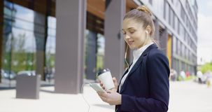 Tevreden meisje gebruikend telefoon en drinkend koffie stock video