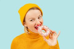 Tevreden mooi meisje die doughnut op pastelkleur blauwe achtergrond eten stock foto's