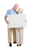 Tevreden oud paar met teken Stock Fotografie
