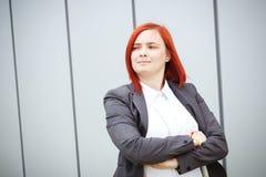 Tevreden succesvolle roodharige meisjeswerkgever, onderneemster in su stock afbeelding