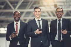 Tevreden werkgevers die mobiles op het werk gebruiken royalty-vrije stock foto's