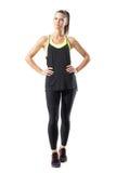 Tevreden zekere actieve gezonde vrouw in sporten die zich met handen op heupen kleden stock afbeelding