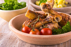 Tew chicken legs on plate in front of  potatoes and green salad Royalty Free Stock Image