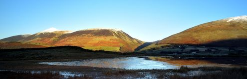 Sunrise on Skiddaw and Latrigg. Tewet Tarn ice and reflections Royalty Free Stock Photography