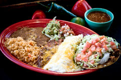 Tex-Mex Combination Plate. A Platter of Tex-Mex Mexican Food with salsa and produce in background stock image