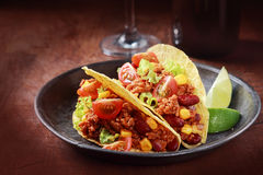 Tex-mex cuisine with corn tacos with meat. Tex-mex cuisine with a serving of two corn tacos with ground meat, salad and vegetable filling in a rustic wooden bowl stock photos