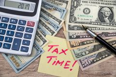 Tex tax time with calculator and money. On desk Stock Photography