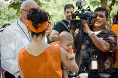 Texan Pro-Choice Protestor. A young woman, holding her infant child, being interviewed at a protest against a Senate Bill that would strictly regulate abortion stock image