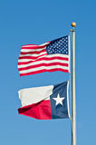 Texas and American Flags. The Texas and American flags flying in tandem on a flagpole against a blue sky Stock Images