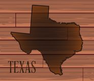 Texas Branded On Wood. A set of medium brown wooden boards as a background to the map of Texas Stock Images